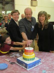 Rev. Erin Splaine, Board Chair Charlie Watts, and Rev. Meghan Cefalu celebrate the 10th anniversary of equal marriage with cake.